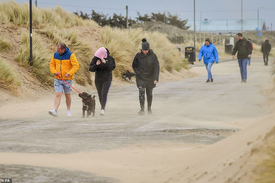 People were blasted by sand in windy conditions in Porthcawl, Wales, on Sunday. One woman is seen pulling a hood over her face to protect her eyes
