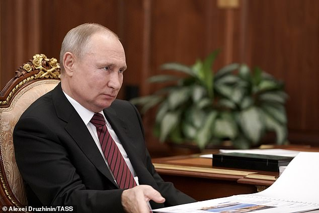 Controversial leader: Putin,a former KGB officer, is pictured here during ameeting with Novgorod Region Governor Andrei Nikitin at the Moscow Kremlin on March 24