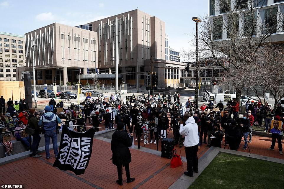 Protesters are seen above outside the courthouse in Minneapolis on Sunday where the former officer charged in George Floyd's death will stand trial