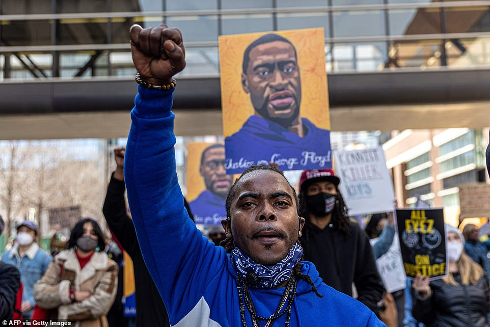 A protester raises his fist while marching in a procession outside Hennepin County Government Center in Minneapolis on Sunday