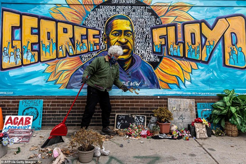 Paul, a volunteer, cleans 'George Floyd Square,' the place where George Floyd died in police custody in May 2020