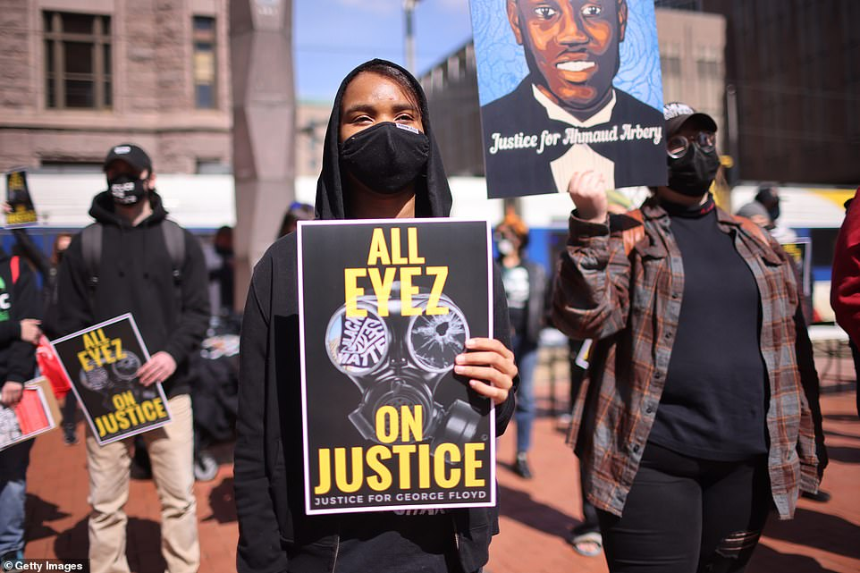 Demonstrators hold up signs that read 'All eyes on Justice - Justice for George Floyd' and 'Justice for Ahmaud Arbery' in Minneapolis on Sunday