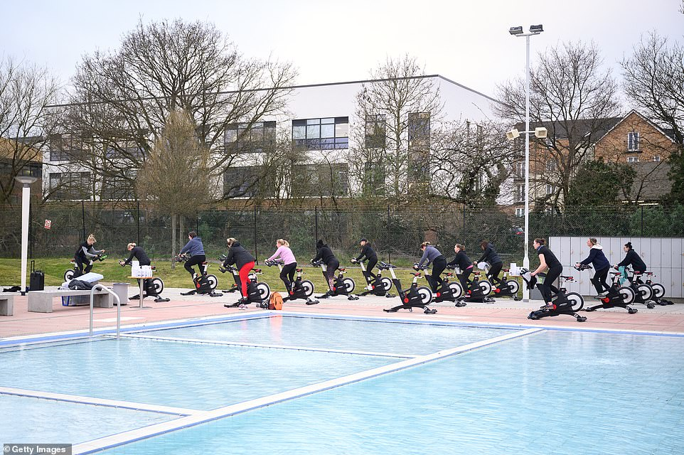 A spin class takes place beside the open-air lido at Hillingdon leisure centre in west London this morning