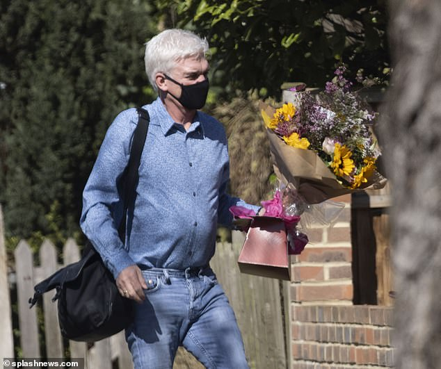 Out and about: The host stepped out in double denim as he held onto the bouquet in west London on Monday after fronting his ITV programme