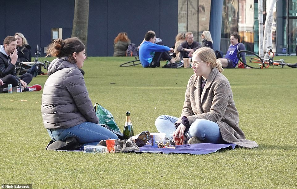 Two friends enjoying a drink in Potter's Fields Park near Tower Bridge amid barmy temperatures for this time of the year