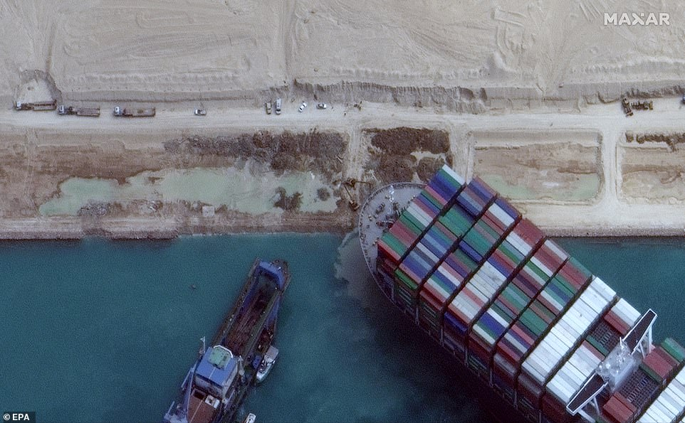 A handout satellite image made available by MAXAR Technologies shows excavation around the bow of the Ever Given and dredging operations in progress, in the Suez Canal, Egypt, March 28, 2021