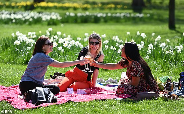 A group of friends enjoy drinks yesterday in beautiful spring weather in St James's Park, central London today as the rule of six was reintroduced
