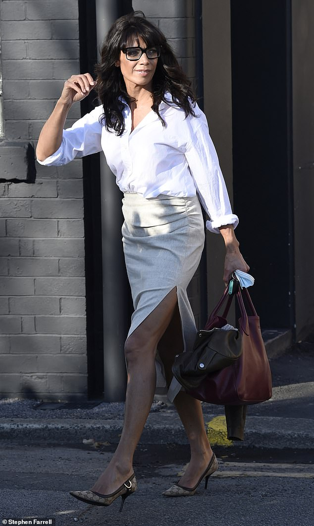 Beauty: The television presenter carried her essentials in a large wine coloured bag while holding her glasses and her face covering in her hand