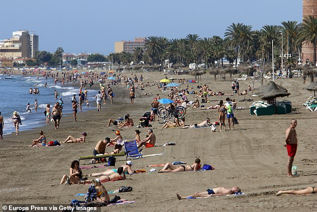 Crowds of people bask in the sun at La Malagueta beach in Spain during the pandemic