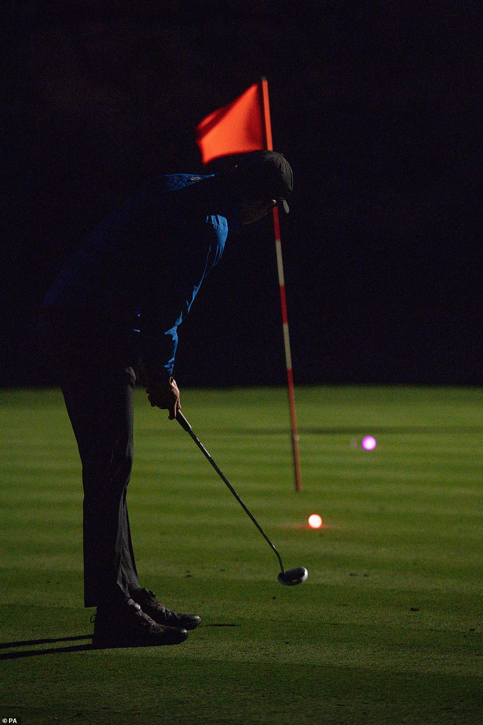 A golfer uses a neon coloured ball whilst under floodlights at Morley Hayes Golf centre in Ilkeston, Derbyshire at just after midnight