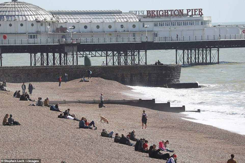 People start to gather on the beach at Brighton around noon today as the coronavirus lockdown begins to ease in England