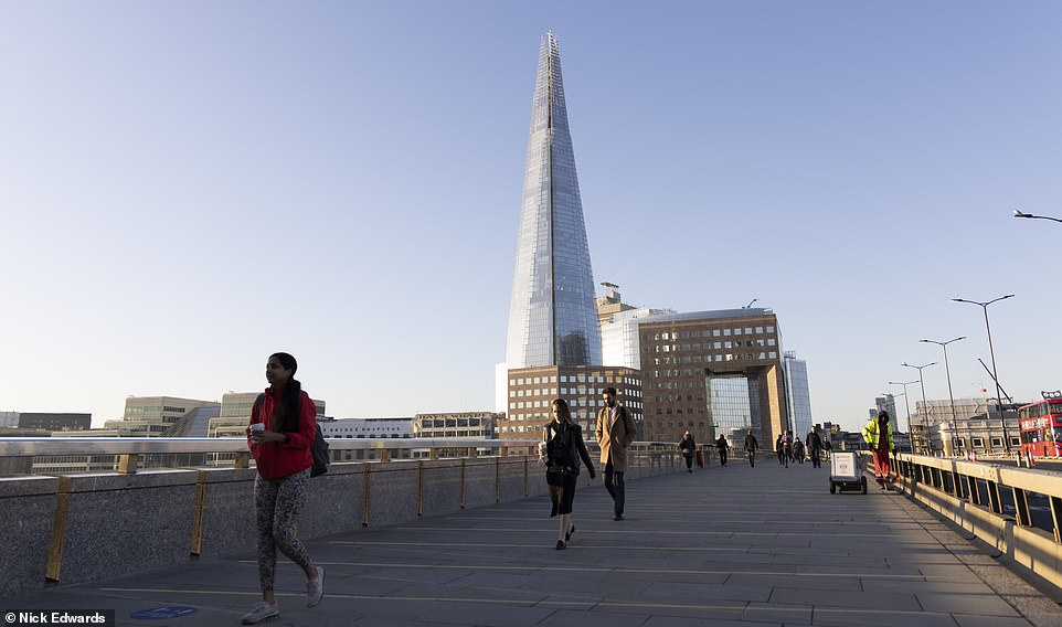 Commuters cross London Bridge in the the morning sunshine today, with temperatures expected to climb throughout the day