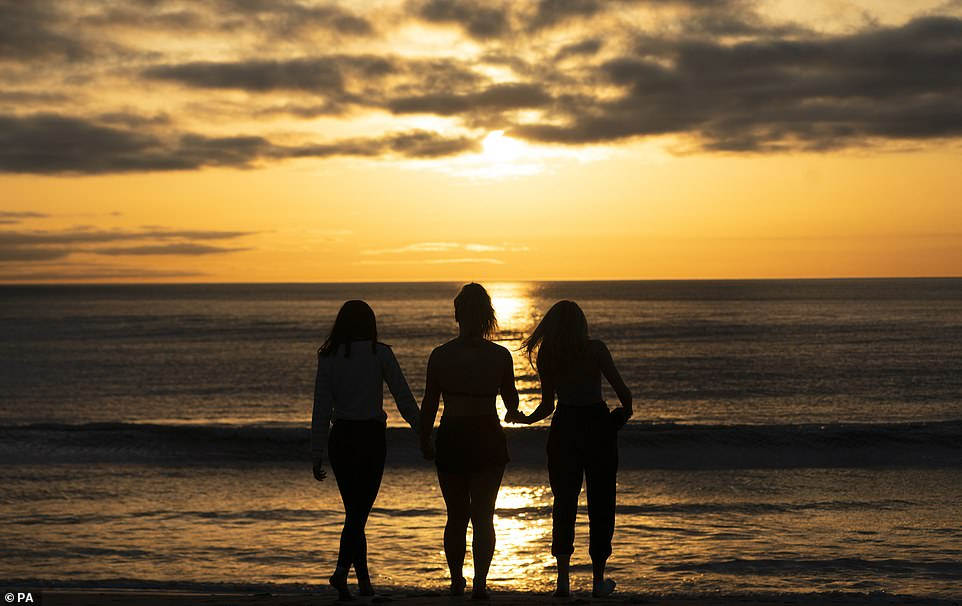 Three friends enjoyed a fresh start to the day as they went for a swim in the North Sea during sunrise at Tynemouth beach