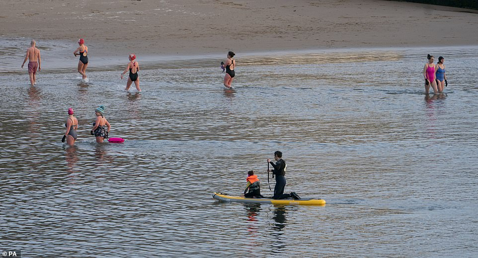 Swimmers take an early morning dip at Cullercoats Bay on the North East coast as the mercury soars in the UK today