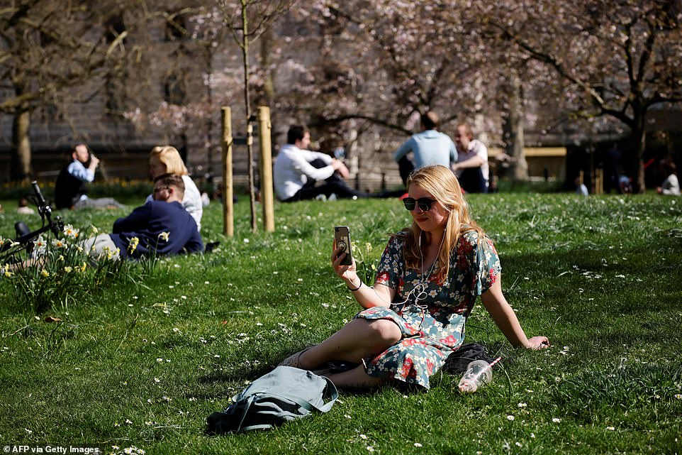 People enjoy the sunshine at St James's Park in London today, one day after it was the joint warmest place in the UK