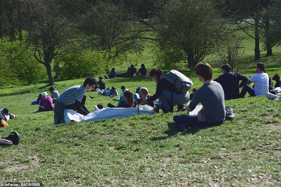 People sit on the grass at Primrose Hill in North London today as they make the most of the pleasant weather conditions