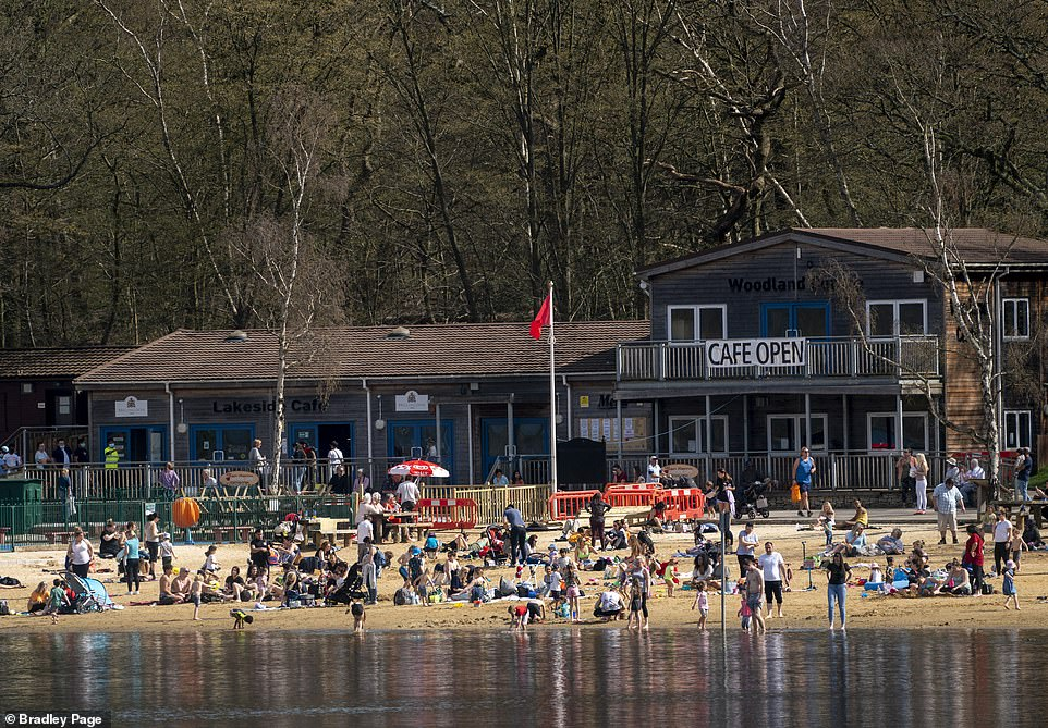 People enjoy the warm weather at Ruislip Lido in North West London this afternoon