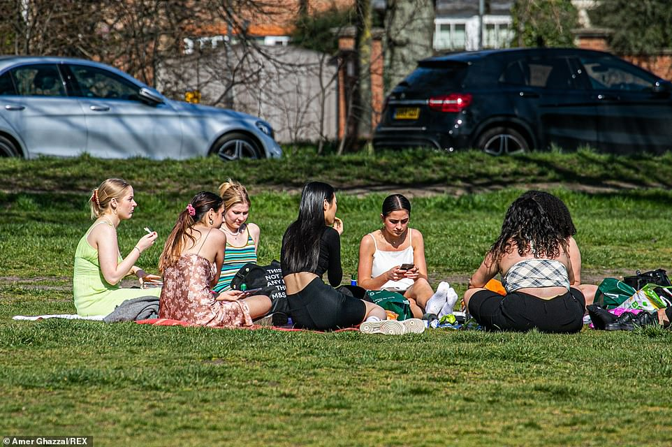 The warm spring sunshine has encouraged people to meet outdoors on Wimbledon Common in South West London today