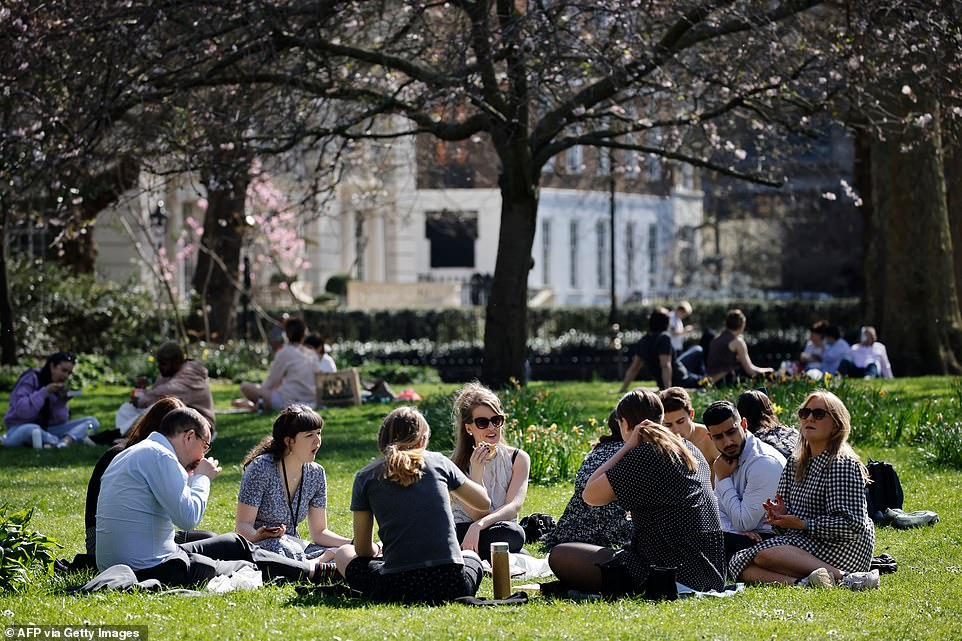 People enjoy the sunshine at St James's Park in London today one day after lockdown restrictions were eased