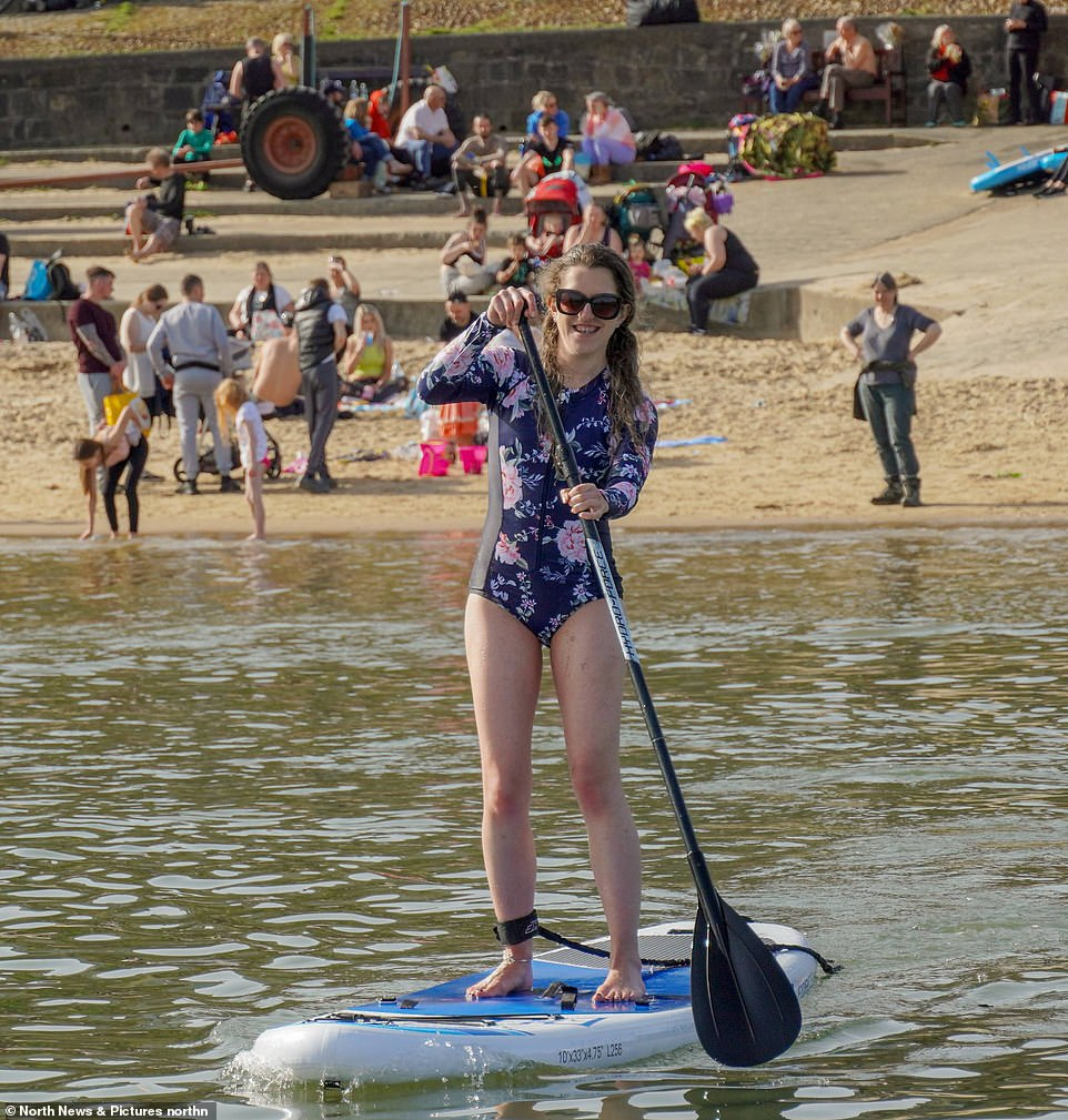 A young woman goes paddle boarding today as people enjoying the hot weather at Cullercoats Bay in North Tyneside