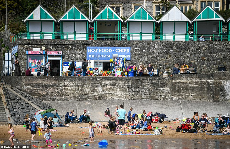 People sit on the sand at Langland Bay in Swansea today on a fine spring day in South Wales
