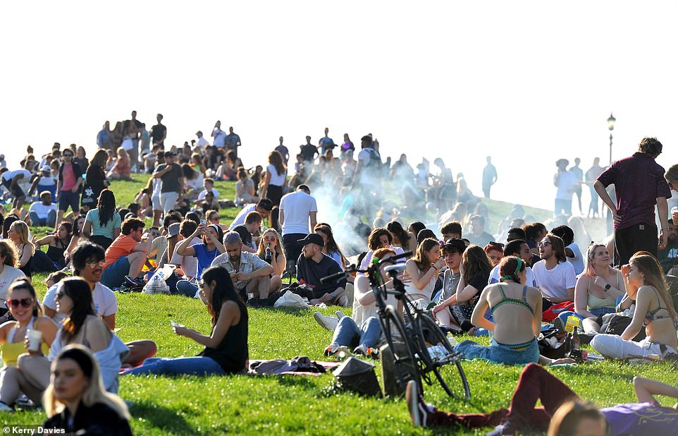 The warmer weather which began yesterday follows a blustery and wet weekend for many - and coincides with the end to the 'stay at home' order in the latest stage of the roadmap out of the third national coronavirus lockdown. Pictured: Huge crowds of revellers on Primrose Hill