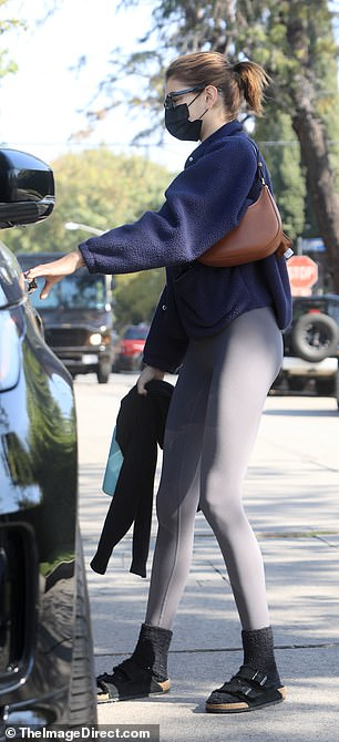 Kaia donned a black shirt with a dark blue jacket layered on top, adding black socks and sandals.
