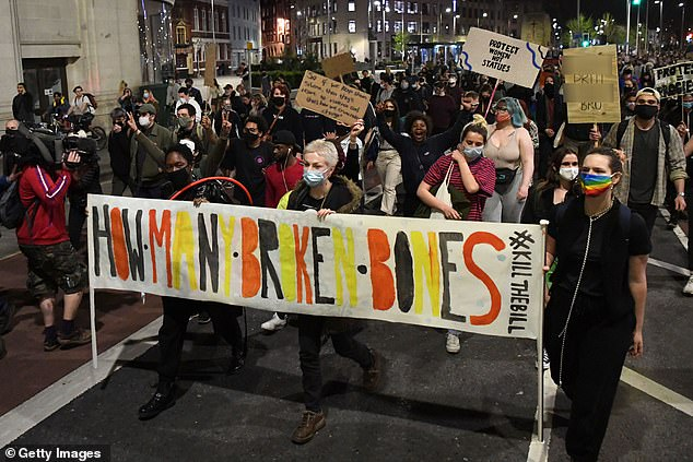 Demonstrators hold up a banner reading 'how man broke bones' as they march to Bridewell Police Station in Bristol during a 'Kill the Bill' protest this evening
