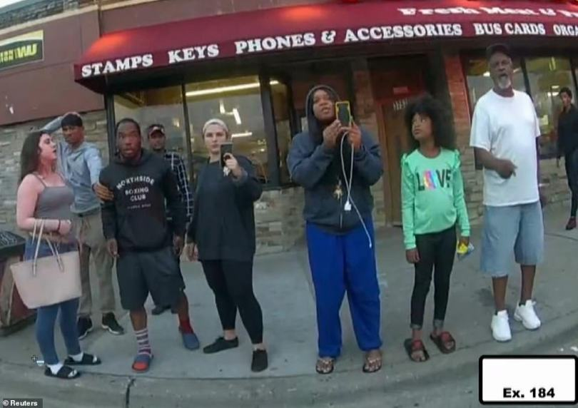 Judea, a nine-year-old witness to George Floyd's death, gave gut-wrenching testimony on Tuesday about how Derek Chauvin refused to remove his knee from the handcuffed black man's neck until paramedics told him to. Judea is pictured second from the right in a green shirt in video from Floyd's fatal confrontation with police that was shown in court