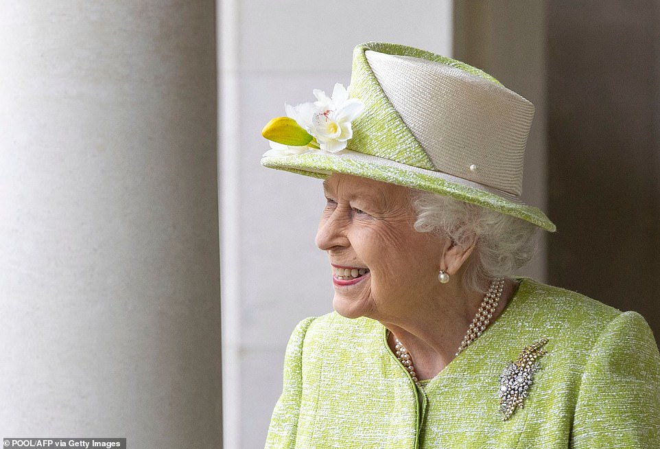 The Queen pinned a broach to her coat and teamed pearl earrings with a matching necklace