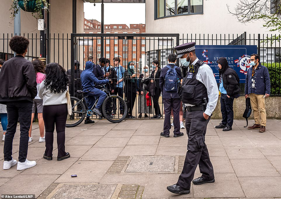Parents and police wait outside the gates of Pimlico Academy yesterday as school children demonstrate in the playground