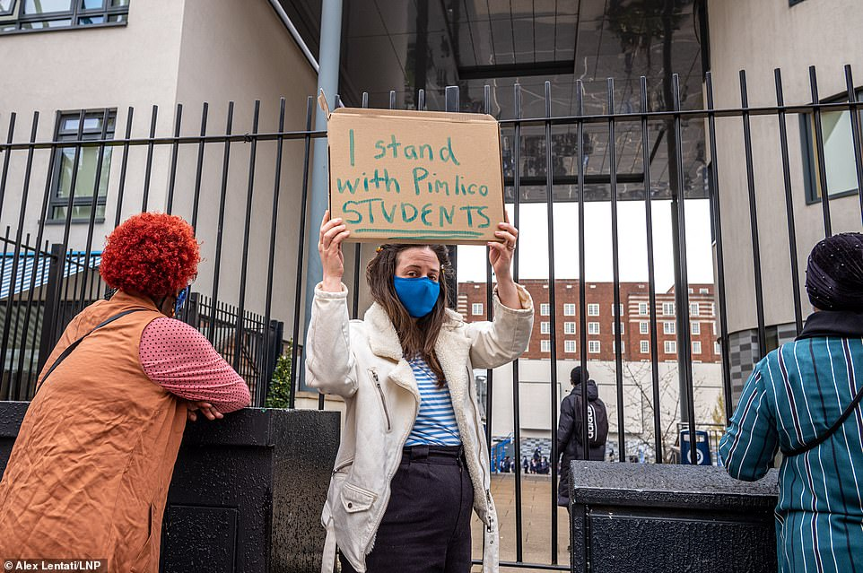 A demonstrator outside the school gates holds up a sign reading: 'I stand with Pimlico students' during the protests yesterday