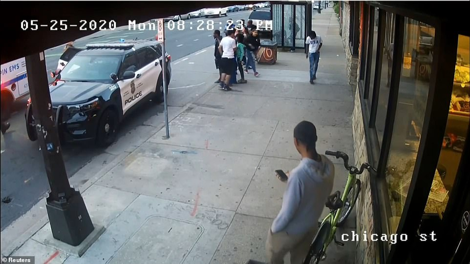 Martin is seen (bottom right) standing outside the store as police restrained Chauvin on the other side of a squad car
