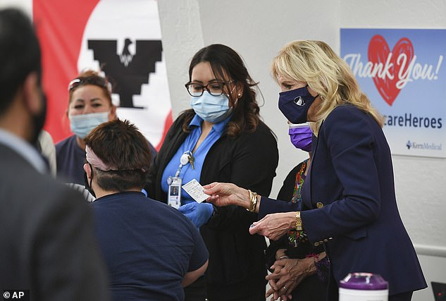 Jill Biden hands out vaccination cards at a vaccination site at The Forty Acres
