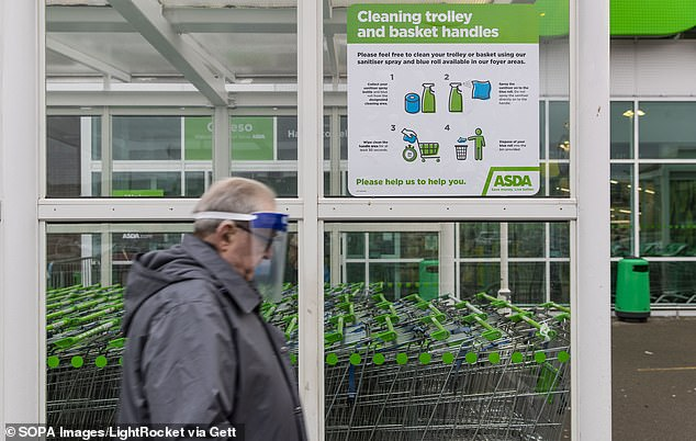 A man wearing a face mask walks pass Covid-19 sign outside an Asda supermarket in Wales