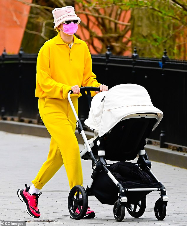 Bringing the sunshine: Gigi Hadid, 25, turns heads in an eye-catching yellow jumpsuit and magenta sneakers while strolling with her newborn daughter Khai in Washington Square Park