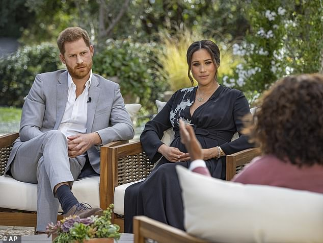 Meghan accused the Royal Family of having 'concerns' about 'how dark' Archie's skin would be before he was born because she is mixed-race and Harry is white in explosive interview Oprah Winfrey (pictured)