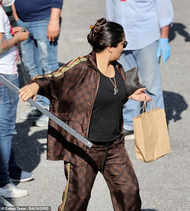 Quick break: Salma stepped out of her trailer holding onto a brown paper bag on Thursday