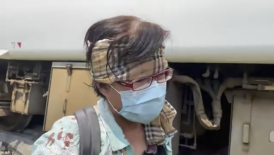 A passengers with a makeshift bandage around his head is seen with blood on his shirt after escaping the crash