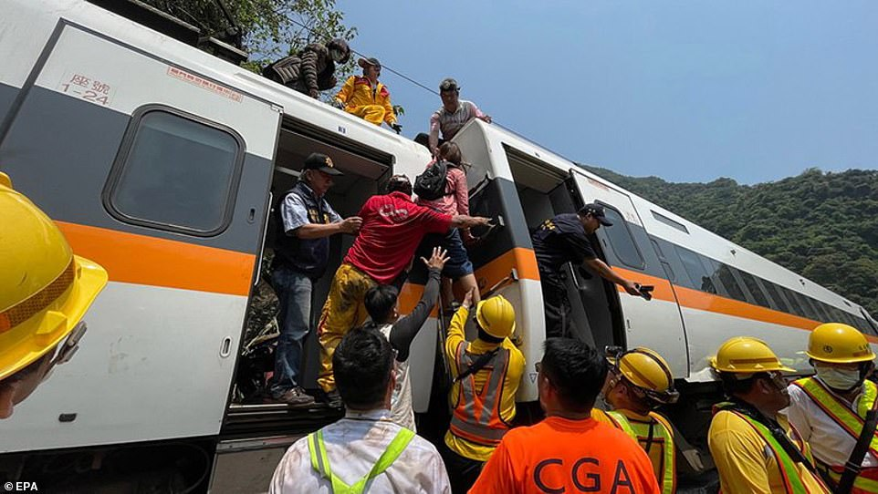 Rescuers help people clamber down from the roof of the train outside the city of Hualien in eastern Taiwan