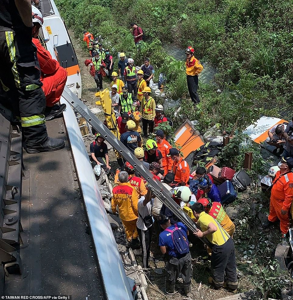 Emergency workers work outside the train beside luggage bags and fragments of train carriage