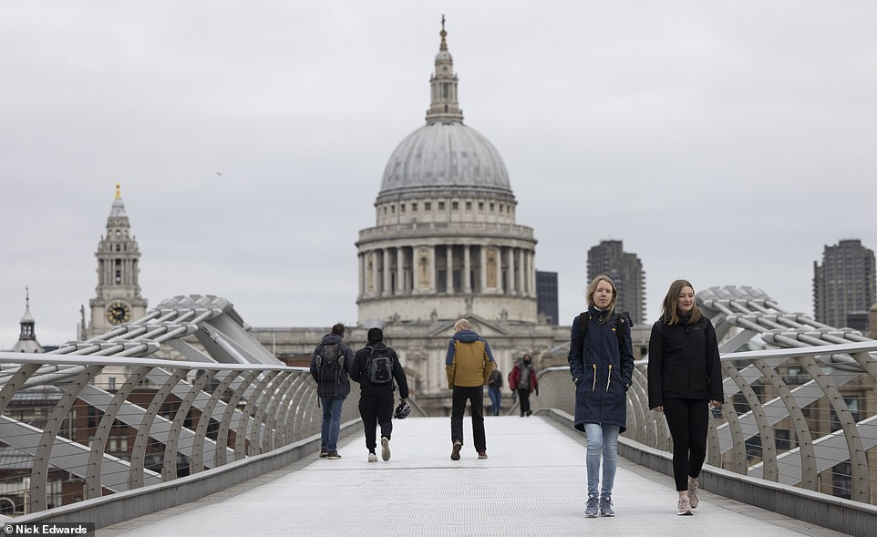 People walk across the Millennium Bridge in London this morning, with St Paul's seen in the background, at the start of the long weekend