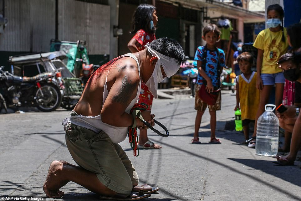 PHILIPPINES: A man whips himself across the back as children watch on during Good Friday celebrations in Manila