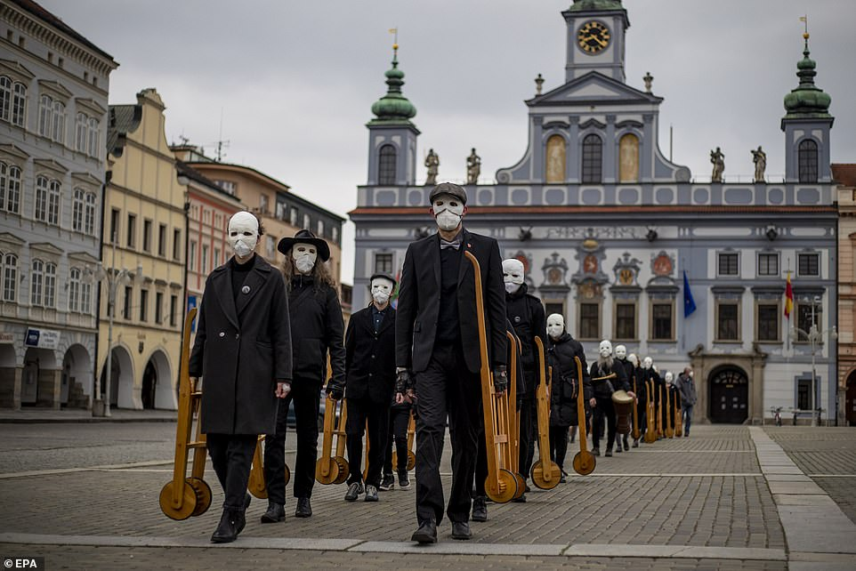 CZECH REPUBLIC: eople wearing masks and respirators and pushing wooden rattles walk through the streets during an Easter procession on Good Friday in the city of Ceske Budejovice