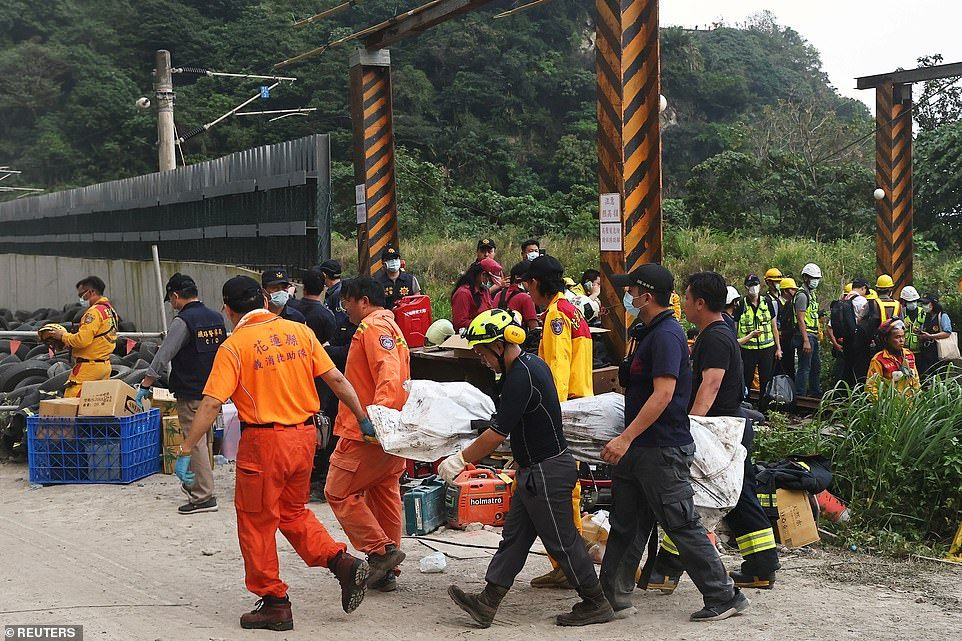 Rescuers carry a body on a stretcher at the site after a train derailed in a tunnel north of Hualien, Taiwan