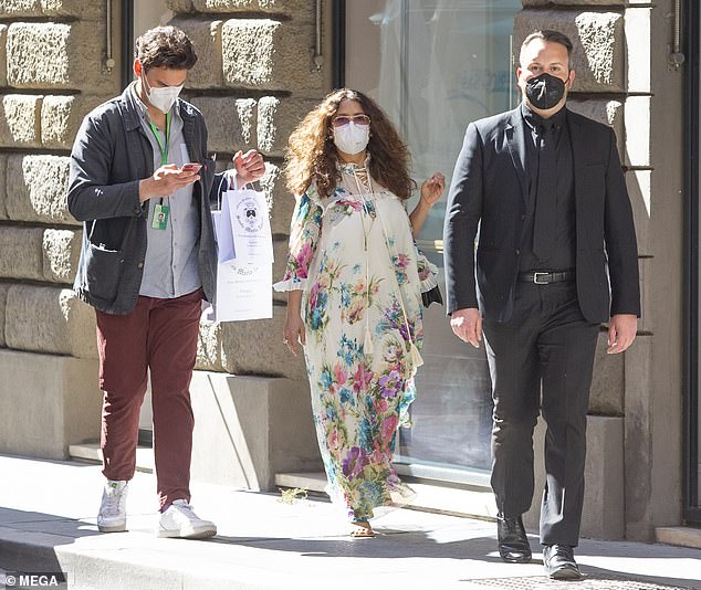 Three's company:The actress, 54, seemed in good spirits as she meandered through the cobbled streets flanked by two male companions
