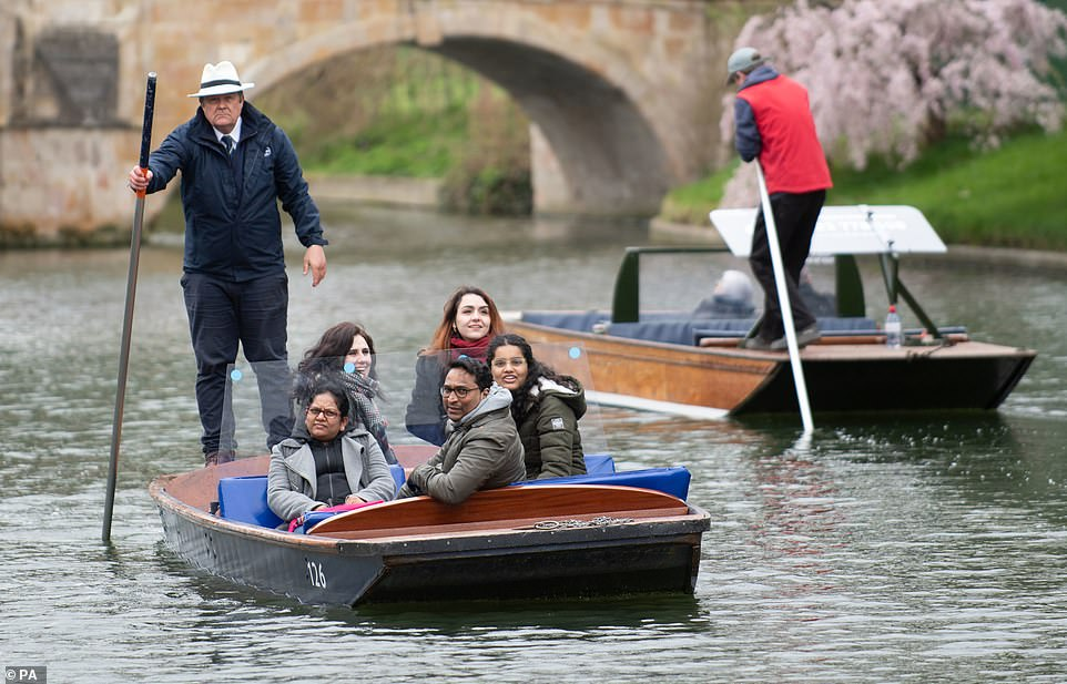 People take a punt tour along the River Cam in Cambridge on a mild day at the start of the extended weekend