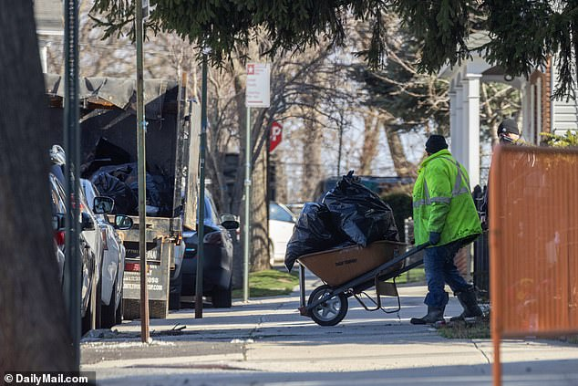 Cleaning crews are seen taking out more garbage from Sakash's home on Friday morning