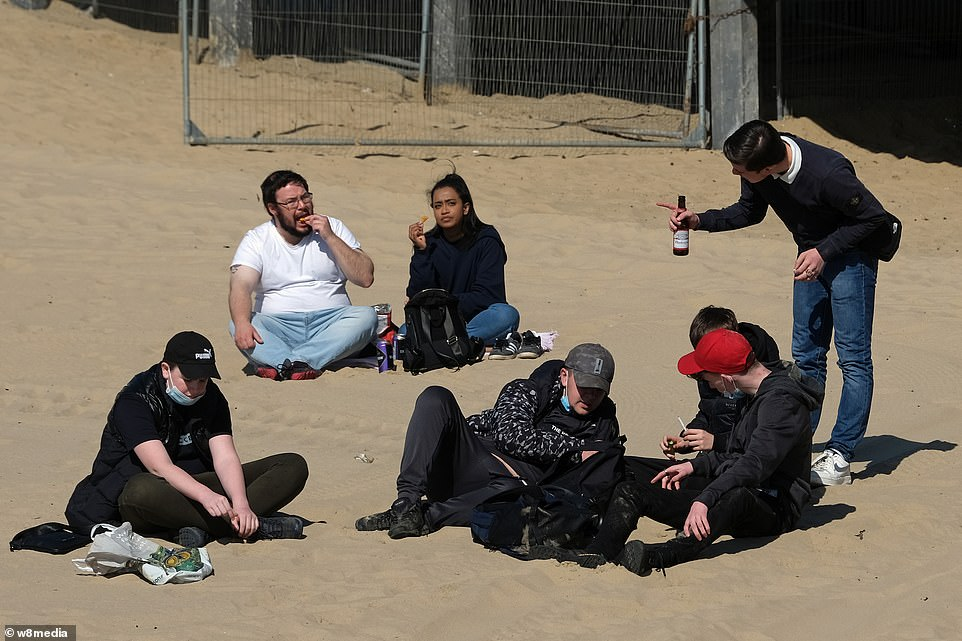 A group of friends gather on the beach in Bournemouth this afternoon to take advantage of the continued sunshine