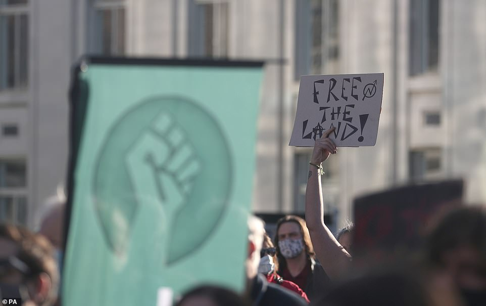 A demonstrator holds up a placard reading 'free the land' during a protest against the Police, Crime, Sentencing and Courts Bill in Guildhall Square, Southampton, today